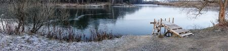 Winter landscape. The frozen lake is covered with new clean ice. panorama