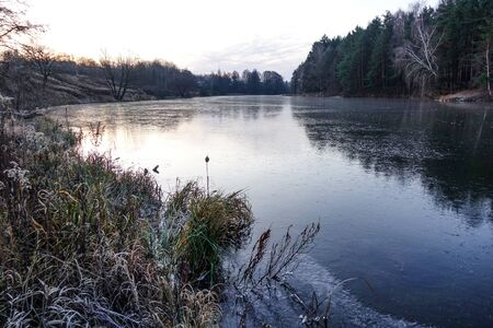 Winter landscape. The frozen lake is covered with new clean ice. Stok Fotoğraf