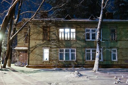 Old wooden house in the winter at night. Glowing window with a cat on the window Stok Fotoğraf