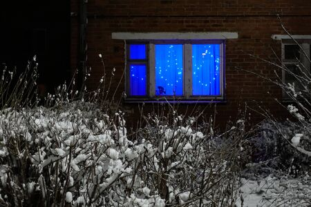 Window of a residential building with a garland. Brick house at night. Feeling of a holiday.