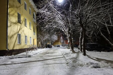 Winter night shot. The yard of a multi-storey building. The yard and trees are covered with snow. Russia