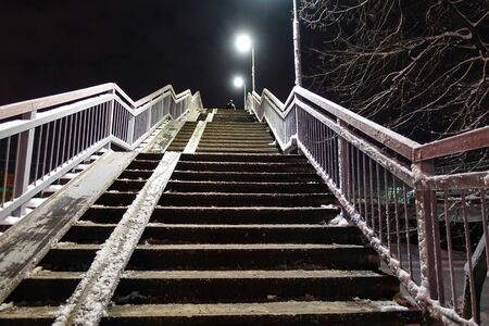 Overpass staircase at night covered in snow. Winter. Russia