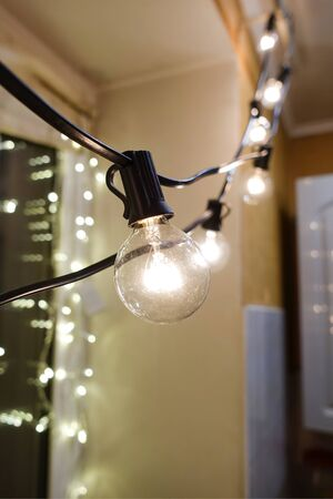 Decoration With Big Bulbs Hanging on a Rope Knot in Apartment. Modern Interior Art.