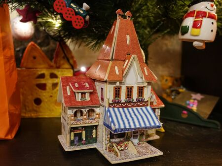 Christmas composition with toys, a wooden house under the tree.