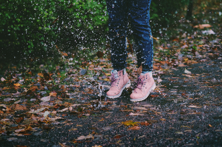 Closeup of a girl splashing the rainwater by jumping into the puddle.