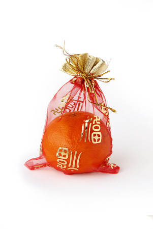 auspicious: Four Oranges, Auspicious Fruits in the red auspicious bag. Chinese gift, isolated on white background.