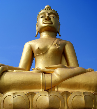 prodigious: Huge golden Buddha Statue is under blue sky.