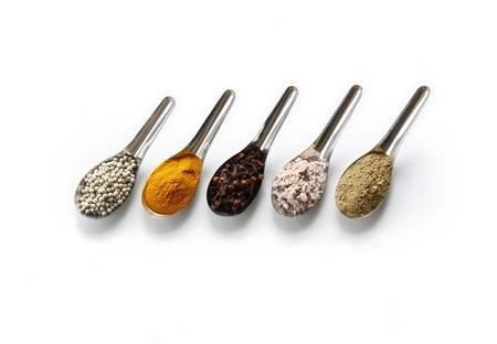 향료. 향신료와 허브 흰색 배경에 고립 된 철강 숟가락. 스톡 콘텐츠