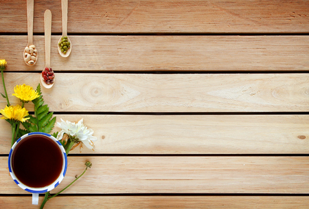 A cup of tea with flowers and tea around it are on wooden background.