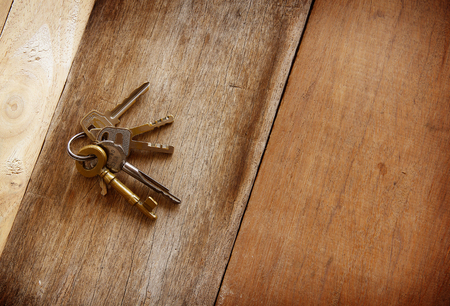 wind down: vintage golden keys are on woonden background. Stock Photo