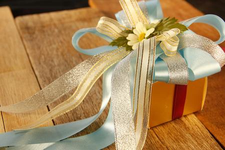 Elegance Golden Gift Box is on Wooden Background.