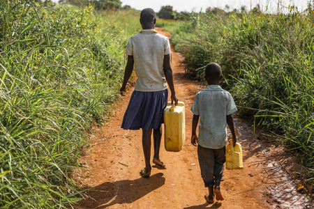 Young boy and girl walk to get water for their village, carrying jerry cans.