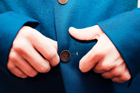 french cuffs: man buttoning a jacket Stock Photo