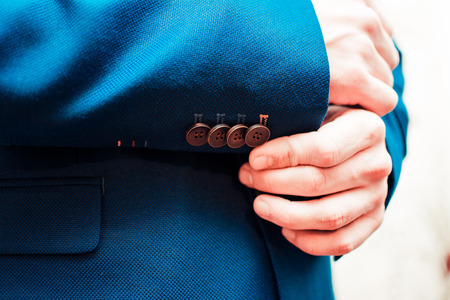 french cuffs: Hands of wedding groom getting ready in suit