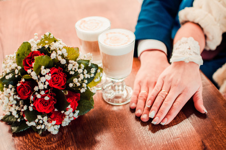 Lady hand holding a white cup of match Latte