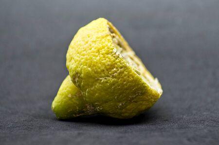 Rotten half lemon isolated on black background