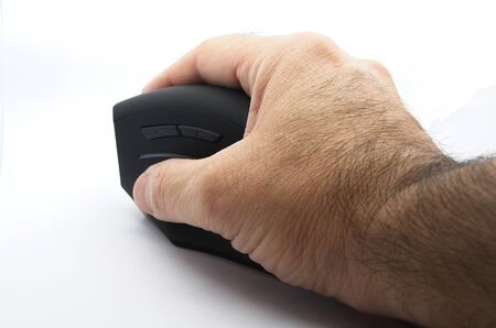 Male right hand holding an ergonomic black mouse on white background.