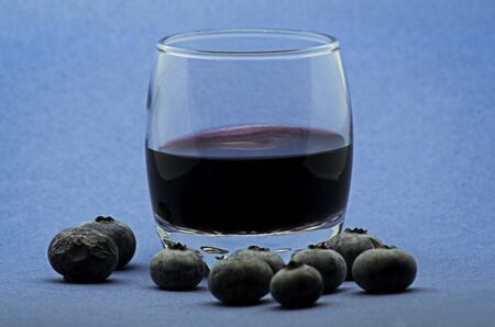 Glass of red wine with blueberries on blue background