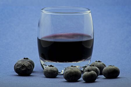 Glass of red wine with blueberries on blue background Foto de archivo - 135502182
