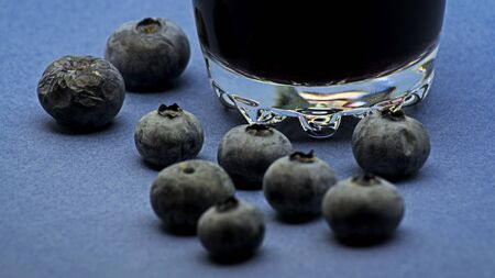 Glass of red wine with blueberries on blue background Foto de archivo - 135502186