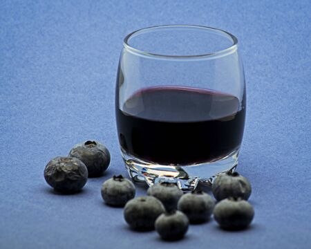 Glass of red wine with blueberries on blue background Foto de archivo - 135502299