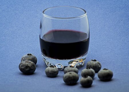 Glass of red wine with blueberries on blue background Foto de archivo - 135502199