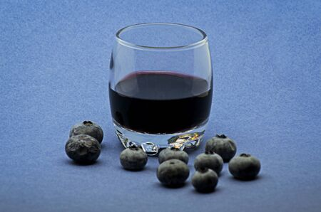 Glass of red wine with blueberries on blue background Foto de archivo - 135502225