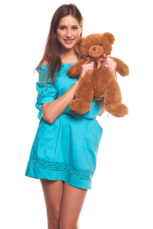 skintight: Pretty girl in blue dress with teddy bear isolate on white background