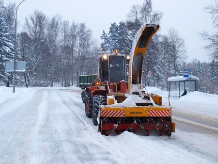SAINT-PETERSBURG, RUSSIA- DECEMBER 12: Snow removal machine with an unidentified driver clean snow-covered road after cyclone called Monica on December 12, 2010 in Saint-Petersburg, Russia