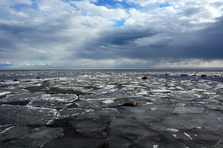Frozen sea shore with stormy clouds and broken ice photo