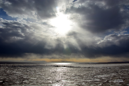 Sun through the stormy clouds at the frozen sea with broken ice photo