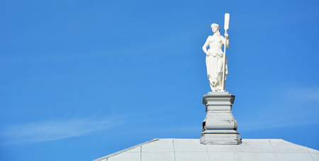 White statue on the roof against blue sky