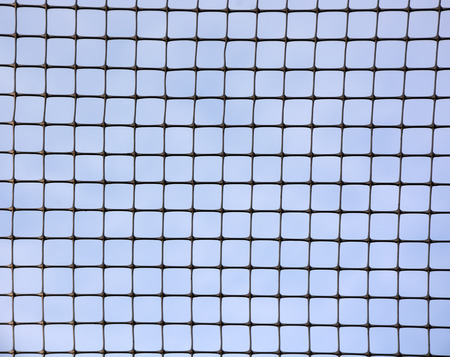 Blue sky behind the metal grid photo