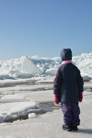 hummock: Little cute girl and Hummock on the frozen sea shore