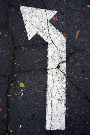 White arrow on traffic surface as a background photo