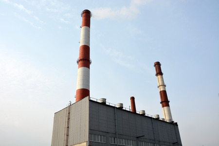 smokestacks: Factory building with smokestacks and blue sky background Stock Photo