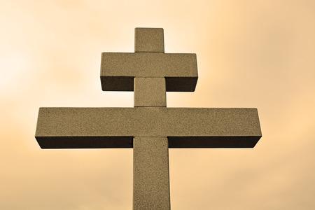 Big cross against the sky in sepia tone photo