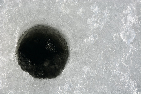 Winter fishing. Ice fishing- hole in the ice photo