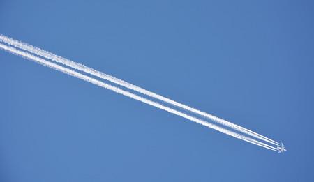 condensation: Traza de condensación partió desde un avión de motor de 4 el cielo azul  Foto de archivo