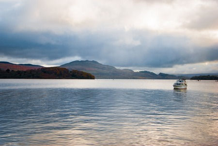 Ice-cold sea with a boat and clouds in Scotland Stock Photo