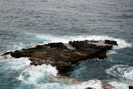 A dark rock in the waves of the ocean