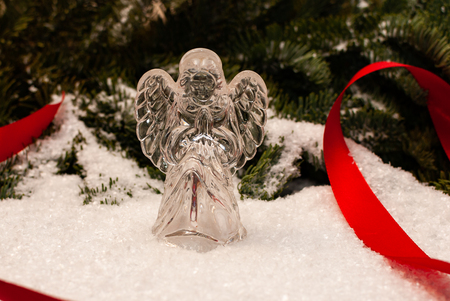 A glass angel standing in the snow looking at you, the forest in the back Stock Photo