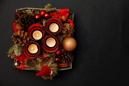 Draufsicht auf Adventskranz mit vier Kerzen, Tannenbaum, Weihnachtskugeln, einem Zwerg und einem Tannenzapfen auf schwarzem Hintergrund Standard-Bild