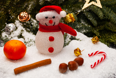 Close up of a toy snowman with a red christmas hat and a red scarf in front of a fir tree, christmas decoration around him