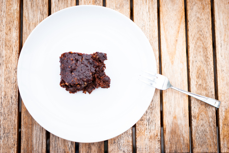 Flat lay of a vegan chocolate brownie laying on a white plate on a wooden table and a fork 版權商用圖片