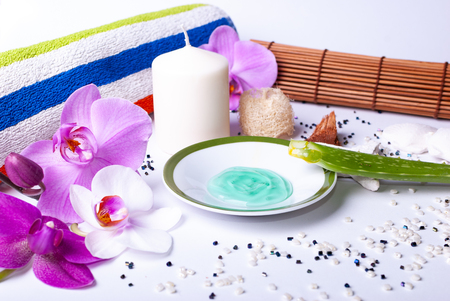 Close up of a set up of wellness items, a candle, stones, a beauty sponge, a sea star, towel, flowers, a natural sponge, aloe vera leave, aloe vera gel, wood, a bamboo mat, decorative stones Stock Photo
