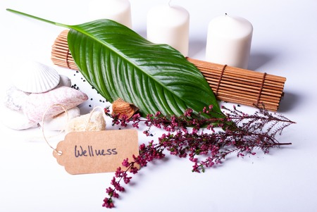 Close up of a set up of wellness items with copy space, a bamboo mat, candles, stones, a branch, a leaf