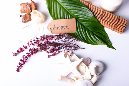 A set up of wellness items, a bamboo mat, a shell, candles, a branch, wood, a starfish and a sign saying Time off in German