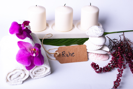 A set up of wellness items, towels, a bamboo mat, a shell, candles, a branch, wood, a starfish Stock Photo