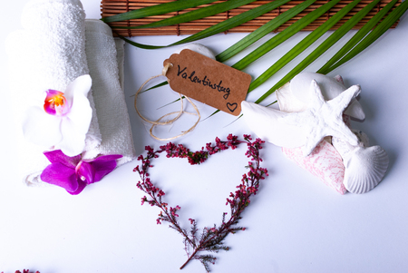 A label saying Valentinstag and colorful red branches, stones, candles, orchids and a bamboo mat and a palm leaf on white background with copy space and two hearts